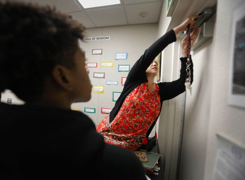 A teacher secures a classroom door during an active shooter drill.