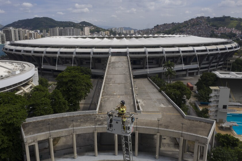 Backdropped by Maracana stadium, firefighter Elielson Silva plays his trumpet from the top of a ladder for residents at home, during a lockdown to help contain the spread of the new coronavirus in Rio de Janeiro, Brazil, Sunday, April 5, 2020. Silva plays tunes known across Brazil, but especially ones composed in and about Rio. (AP Photo/Leo Correa)