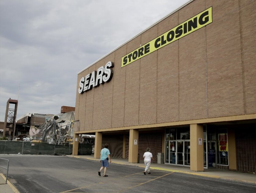 FILE- In this July 8, 2017, file photo people walk into a Sears store slated for closing that is next to a mall that is being torn down in Overland Park, Kan.