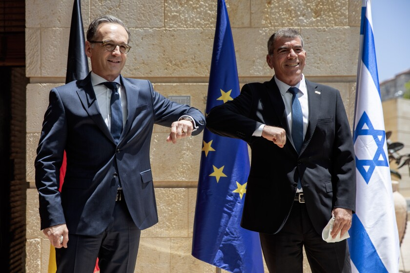 CORRECTS SPELLING OF GERMAN FOREIGN MINISTER TO MAAS - Israeli Foreign Minister Gabi Ashkenazi, right, welcomes his German counterpart Heiko Maas with a elbow bump due to the coronavirus outbreak, prior to their meeting in Jerusalem, Wednesday, June 10, 2020. (AP Photo/Oded Balilty)