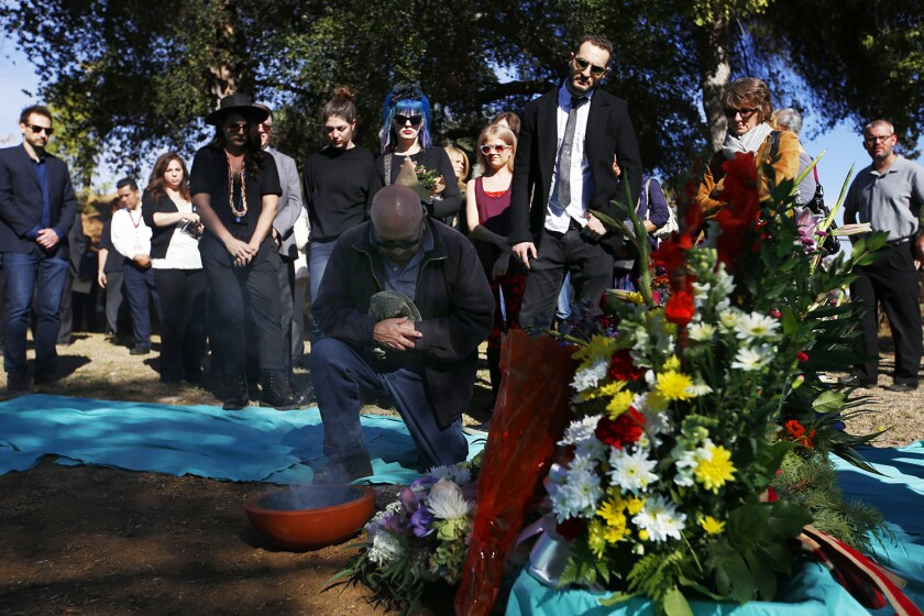 """Rafael Sarabia, 79, of Hawthorne,kneels quietly at the site of a mass grave of L.A. County's unclaimed dead. He said he came to the ceremony because """"no one should be left alone."""""""