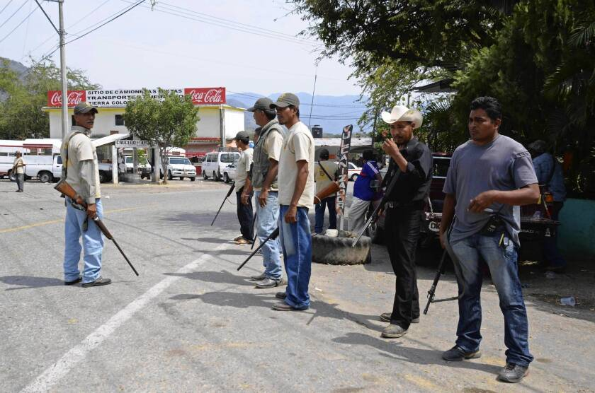 "Citizen vigilantes stand at the entrance to Tierra Colorada, in Guerrero state on Mexico's Pacific Coast. A federal official called the decision by the anti-drug-cartel vigilantes to join in political protests a ""Molotov cocktail."""