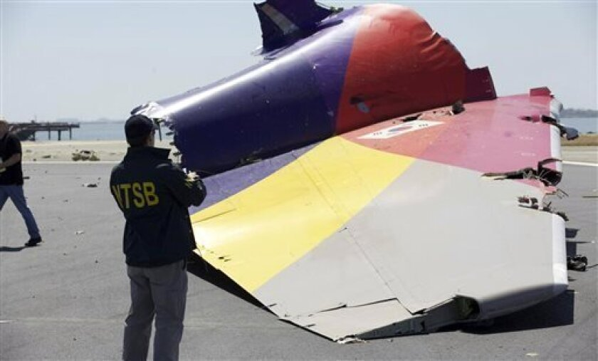 This image released by the National Transportation Safety Board, Sunday, July 7, 2013, shows an NTSB agent photographing a part of the Boeing 777 Asiana Airlines Flight 214 aircraft. The Asiana flight crashed upon landing Saturday, July 6, at San Francisco International Airport, and two of the 307 passengers aboard were killed. (AP Photo/NTSB)
