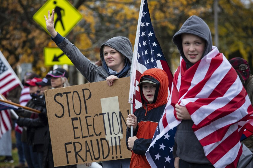 """FILE - In this Saturday, Nov. 14, 2020 file photo, supporters of President Donald Trump hold signs as they attend a """"Stop The Steal"""" rally, protesting the outcome of the presidential election, at the Oregon State Capitol in Salem, Ore. After a 2020 election cycle dominated by conspiracy theories and false claims about voting, top election officials across the country are looking ahead to future elections and grappling with how they can counter a wave of misinformation that led to violent threats against them and ultimately a deadly riot at the Capitol. (AP Photo/Paula Bronstein)"""