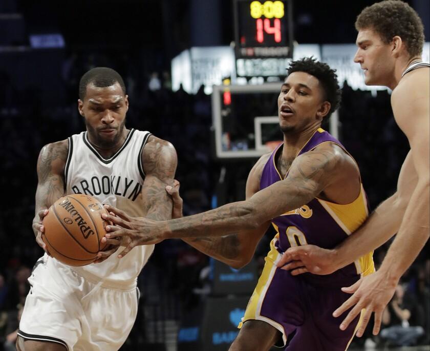 Sean Kilpatrick, de los Nets de Brooklyn, dribla a Nick Young, de los Lakers de Los Ángeles, durante la segunda mitad del partido del miércoles 14 de diciembre de 2016 (AP Foto/Frank Franklin II)