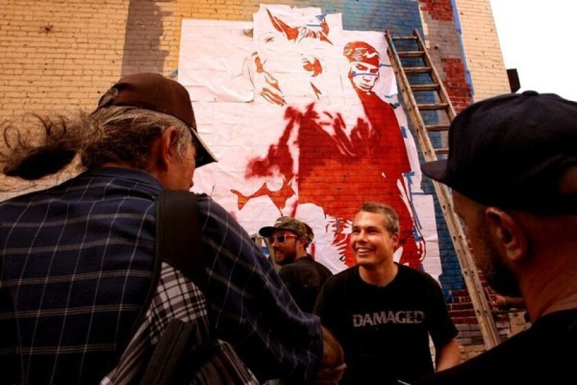 Shepard Fairey, center, greets fans in Los Angeles in August.