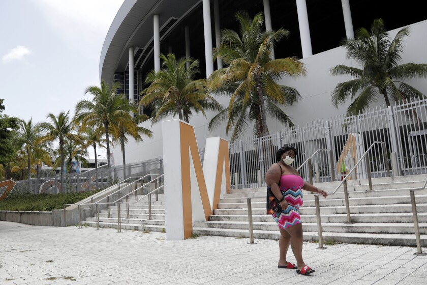 A woman wearing a protective face covering walks past Marlins Park on Monday in Miami.