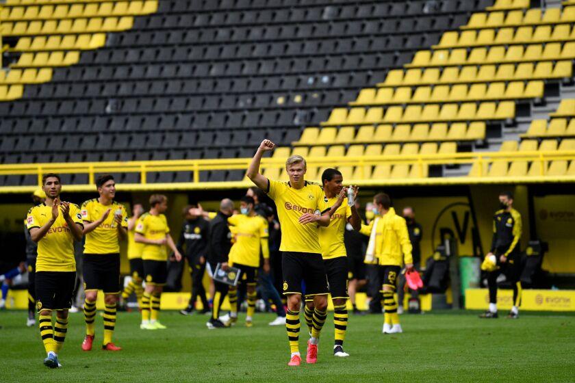 Borussia Dortmund's Erling Haaland, center, and his teammates celebrate winning the German Bundesliga soccer match between Dortmund and Schalke in Dortmund, Germany, on Saturday.