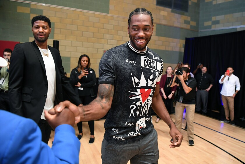Kawhi Leonard and Paul George make their way to the stage before their introductory news conference with the Clippers.