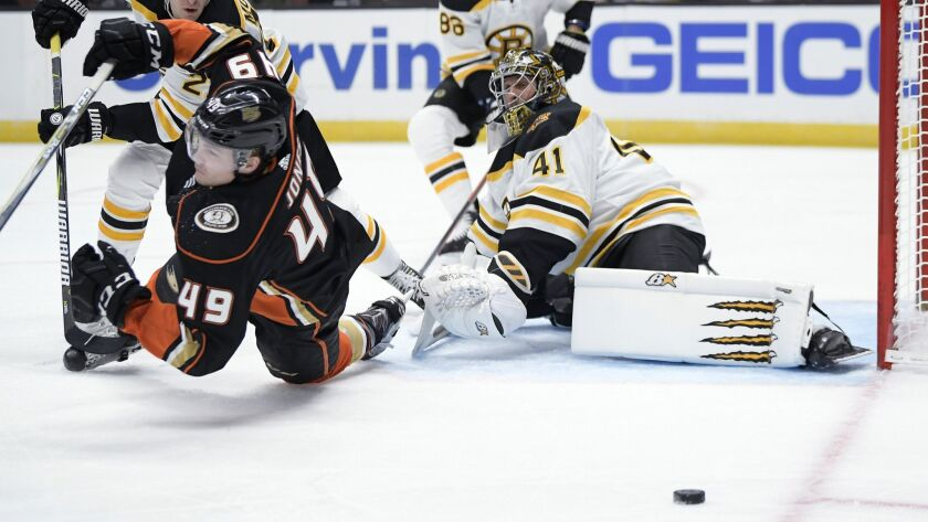 Boston Bruins goaltender Jaroslav Halak, right, deflects a shot as Ducks left wing Max Jones, left, falls during the second period.