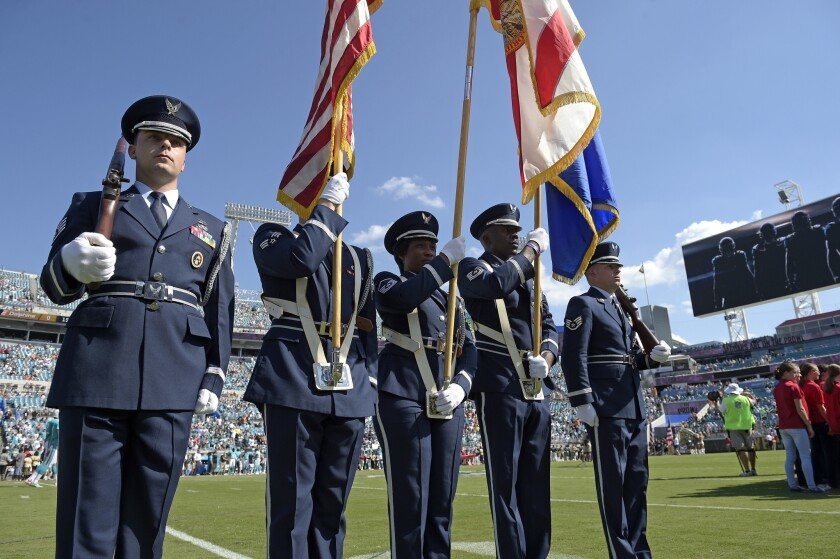 A military color guard stands at attention for the singing of the national anthem before an NFL game between the Dolphins and the Jaguars in Jacksonville, Fla., on Sept. 20, 2015.