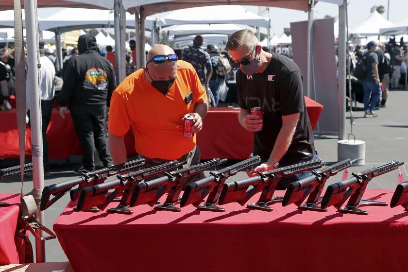 Gun enthusiasts check out sporting rifles at a gun show in Costa Mesa.