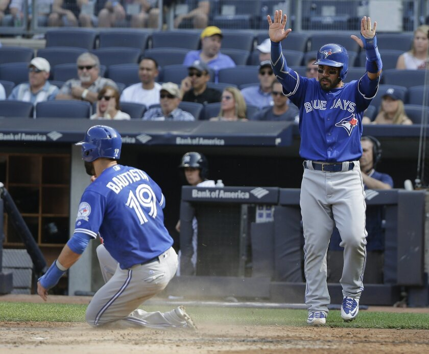Toronto Blue Jays' Devon Travis, right, raises his hands as Jose Bautista (19) scores on a base hit by designated hitter Edwin Encarnacion during the third inning of a baseball game against the New York Yankees, Thursday, May 26, 2016, in New York. (AP Photo/Julie Jacobson)