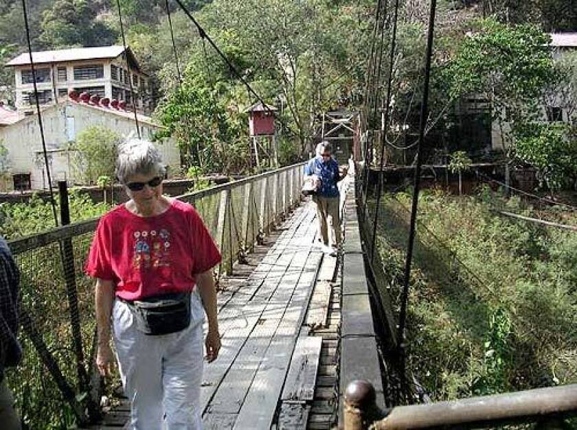 Leanne Blinzler Noe, front, walks across a bridge to revisit her childhood home in Baguio with her friend Dorothy Mullaney Brooks, who was her roommate in a Manila prison camp.