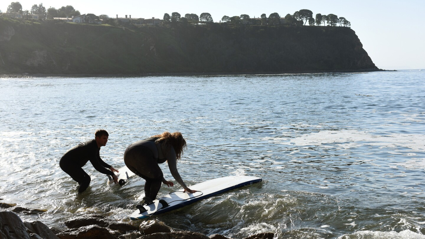 Brian Jones of Los Angeles and Mimi Miller of the South Bay head out to surf.