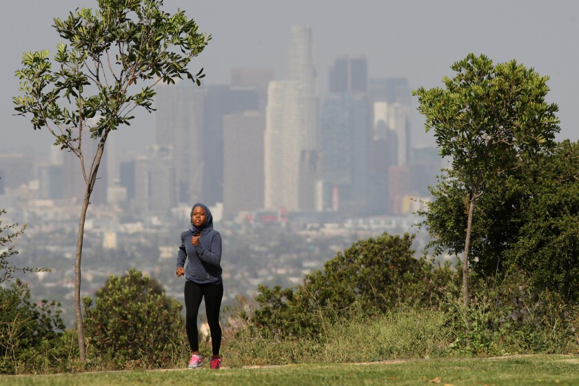 With downtown Los Angeles in the background, a woman runs near the Bowl Loop at Kenneth Hahn State Recreation Area.