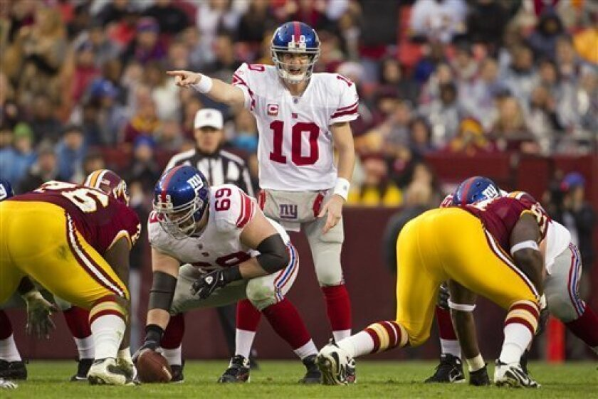New York Giants quarterback Eli Manning (10) directs the offense during the first half of an NFL football game against the Washington Redskins on Sunday, Jan. 2, 2011, in Landover, Md. (AP Photo/Evan Vucci)