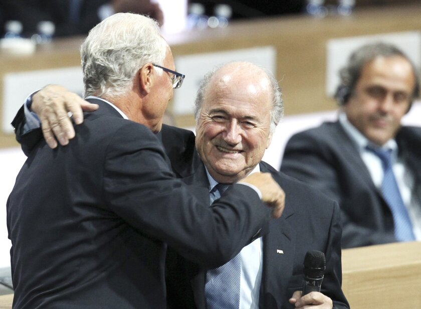 FILE - In this June 1, 2011 file photo FIFA President Joseph Blatter reacts when is hugged by German soccer legend Franz Beckenbauer, left, after he was re-elected FIFA president  in Zurich, Switzerland. The adjudicatory chamber of FIFA's Ethics Committee on Thursday, Feb. 17, 2016 has imposed a sa