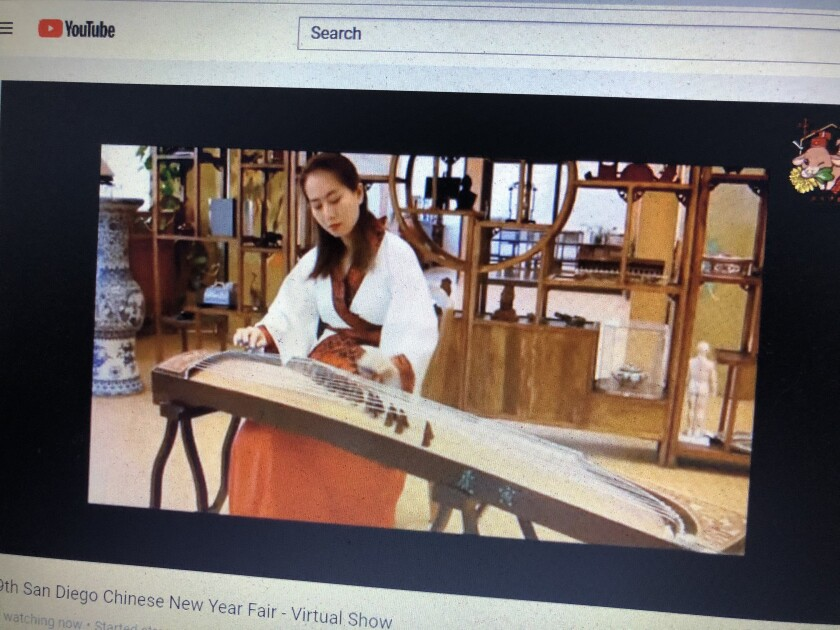 """As part of the Chinese New Year celebration a woman performs """"The Fisherman's Song at Dusk"""" on the Guzheng"""