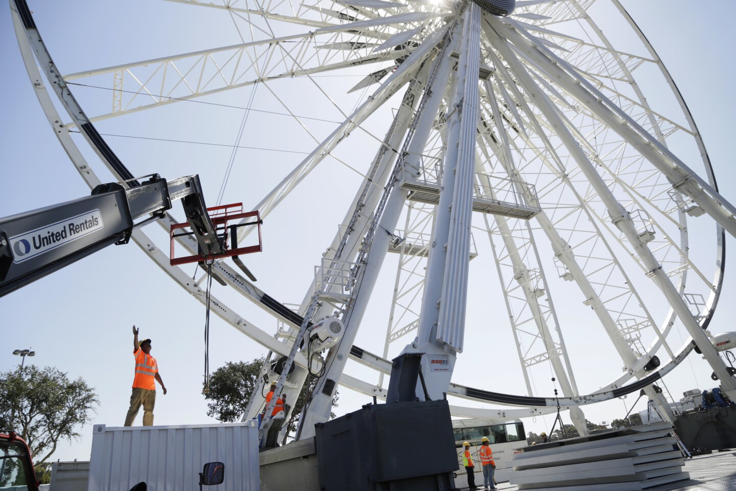 Nabeel Meyer directs a forklift as a large Ferris wheel is set up for this year's Orange County Fair in Costa Mesa, which will run from Friday to Aug. 11.