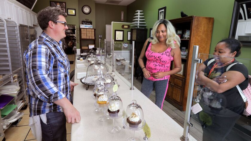 Don Hein, owner of Little Cakes Cupcake Kitchen, assists customers Jackie Brown, left, and friend Latoya James, at right, as they decide which cupcakes they want.