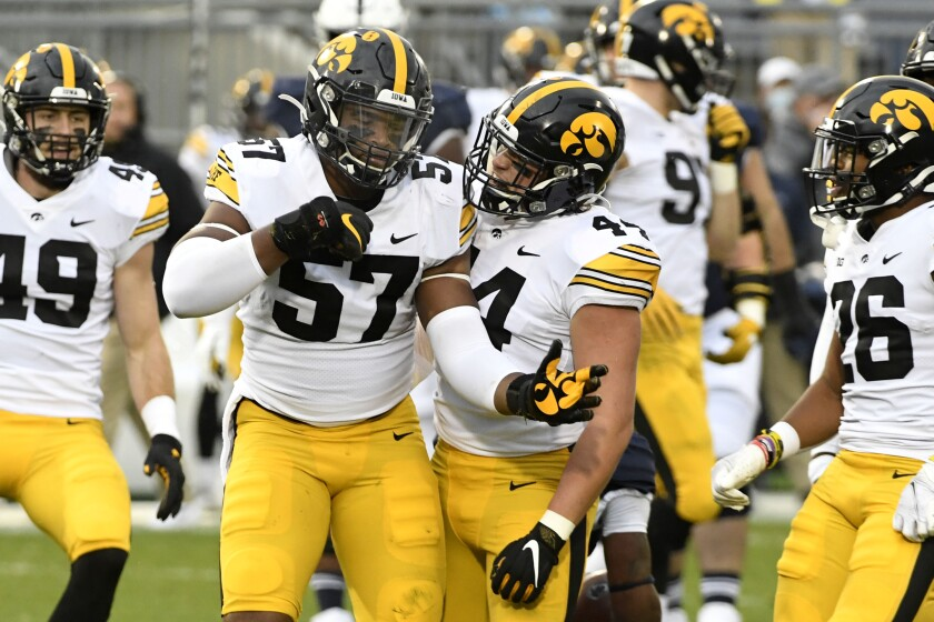 Iowa defenders Chauncey Golston (57) and Seth Benson (44) celebrate after tackling Penn State quarterback Will Levis (7) in the first quarter of an NCAA college football game in State College, Pa., on Saturday, Nov. 21, 2020.Iowa defeated Penn State 41-21. (AP Photo/Barry Reeger)