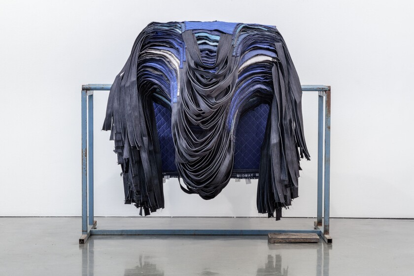 """Rack of Aprons"" by Theaster Gates, 2019. Restitched moving mats, still rack, bronze, 52.5 inches by 54 inches by 60 inches."