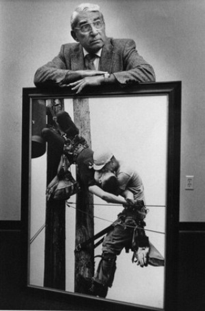 """Rocco Morabito, who won the 1968 Pulitzer Prize for spot news photography for """"Kiss of Life,"""" poses in Jacksonville, Fla., in 1988, with the photo. It shows J.D. Thompson giving mouth-to-mouth resuscitation to his fellow Florida power company lineman R.G. Champion, who had received a 4,160-volt electric shock after coming in contact with a hot wire atop a utility pole. Champion survived."""