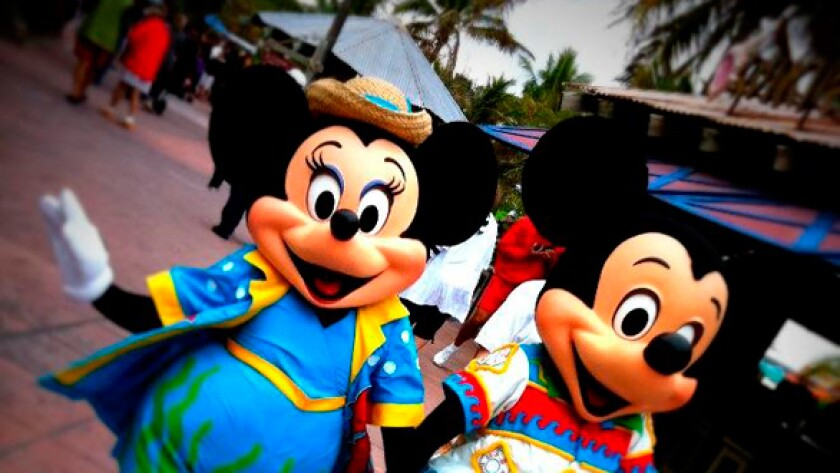 Minnie and Mickey Mouse walk around Castaway Cay, a stop on the Disney Dream cruise.