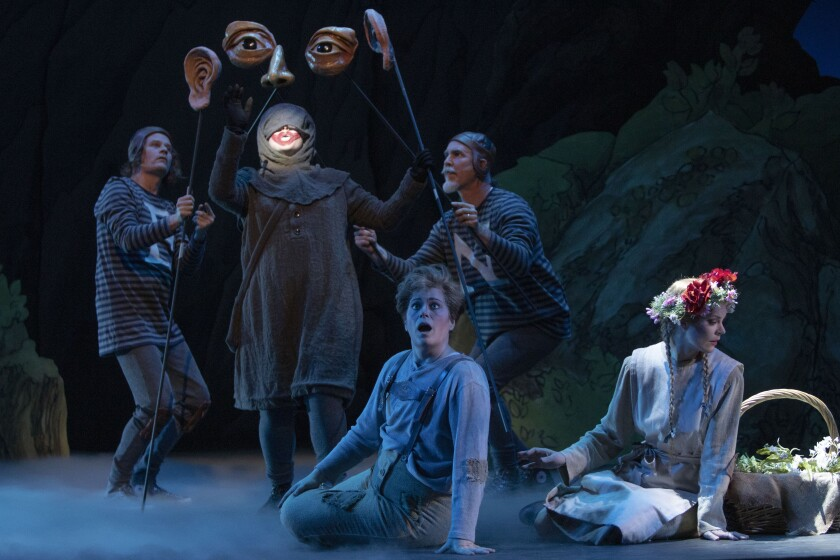 """Soprano Devon Guthrie (center, rear) is the Sandman, mezzo-soprano Blythe Gaissert (seated, center) is Hansel, and soprano Sarah Gartland (right) is Gretel in San Diego Opera's """"Hansel and Gretel"""" at the San Diego Civic Theatre. Also pictured are puppeteers Jason James Johnson (left) and Iain Gunn."""