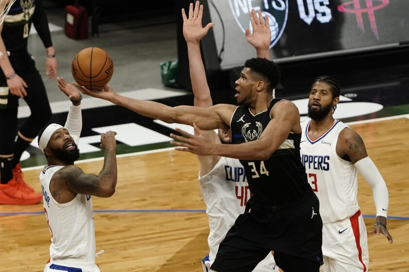 Milwaukee's Giannis Antetokounmpo drives for a layup in front of the Clippers' Marcus Morris, Ivica Zubac and Paul George.