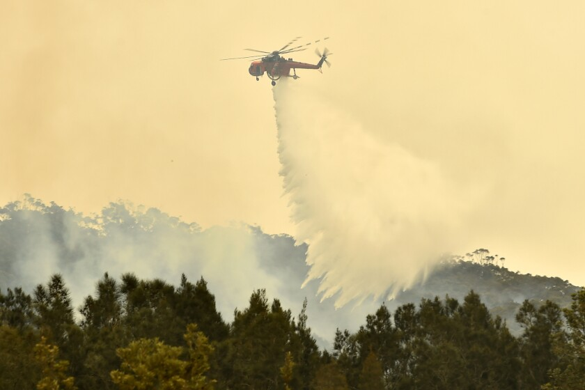 A helicopter dumps water on a wildfire outside the town of Batemans Bay in New South Wales, Australia, on Thursday.
