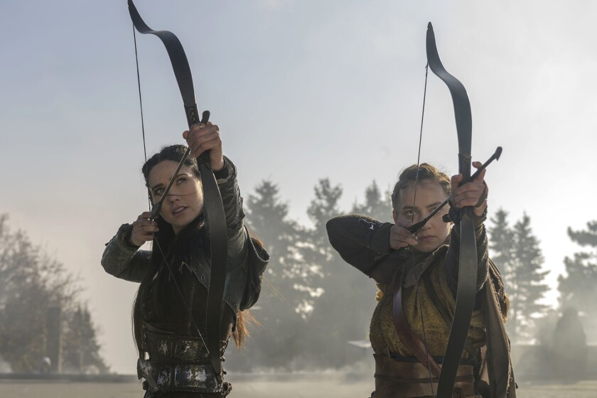 Two young archers notch arrows and draw their bows.