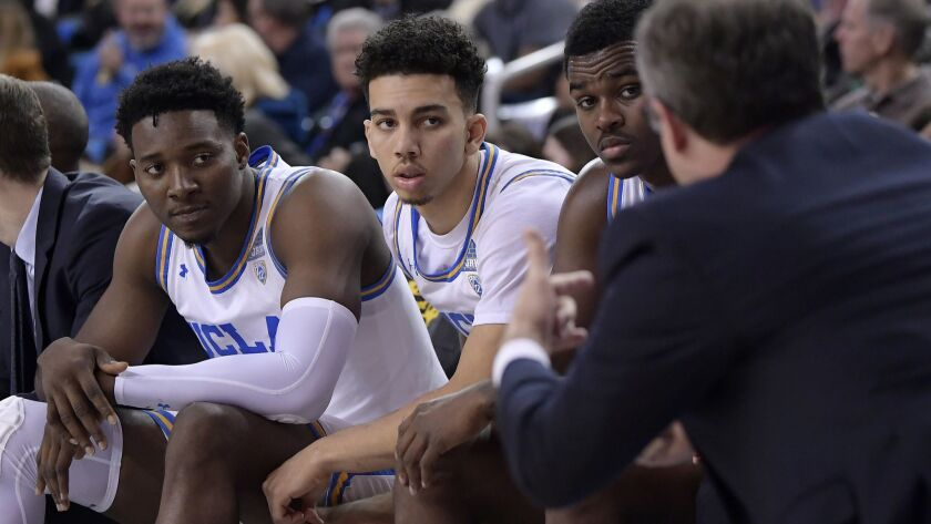 UCLA interim coach Murry Bartow, right, talks to his team during the second half against Stanford on Thursday. UCLA won 92-70.