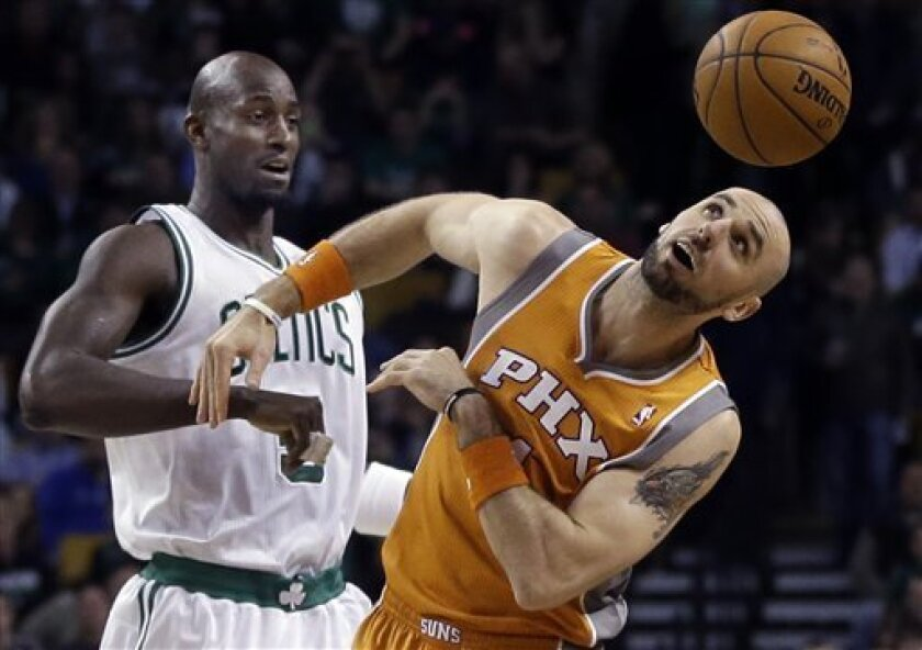 Phoenix Suns center Marcin Gortat, right, watches the ball after the tipoff against Boston Celtics power forward Kevin Garnett, left, during the first quarter of an NBA basketball game in Boston, Wednesday, Jan. 9, 2013. (AP Photo/Elise Amendola)