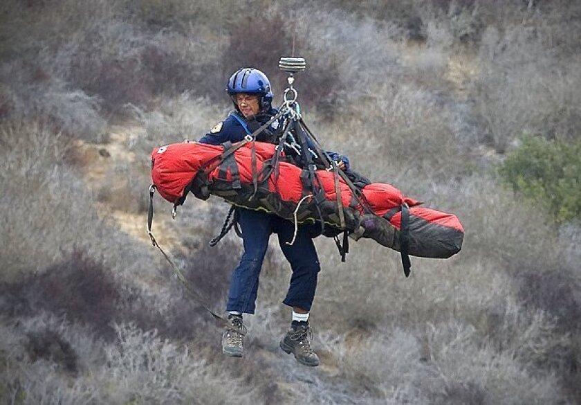 San Diego Fire Department Copter-2 pulls up one of the two injured victims along with flight medic Barry Links from the ravine rescue at Cabrillo National Monument. The 91-year-old Harold Reed was lifted out from the wreckage and air transported directly to the hospital.