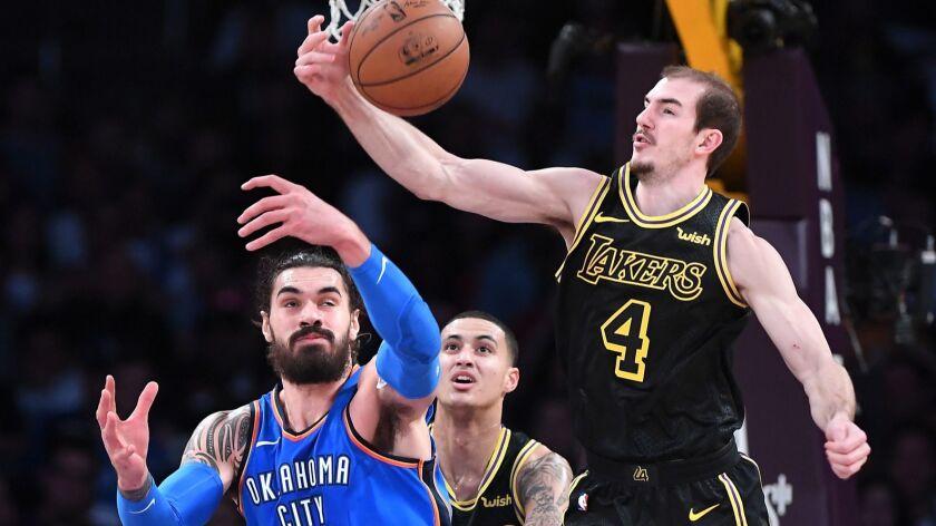 Lakers guard Alex Caruso intercepts a pass intended for Thunder center Steven Adams during a game last season.