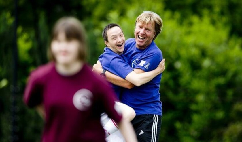 """A child with Down syndrome hugs a trainer during a soccer tournament """"Give Down a future"""" in Amsterdam."""