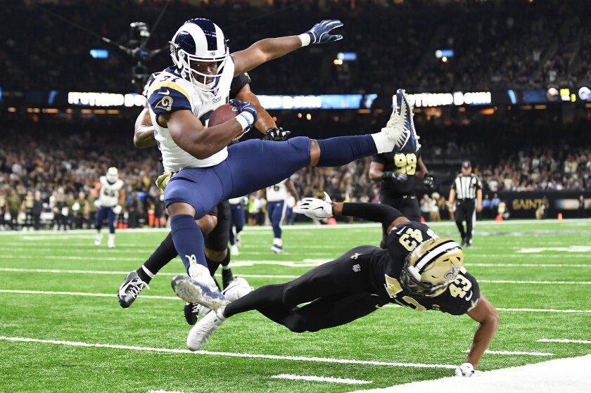 The Rams' Malcolm Brown leaps over Saints safety Marcus Williams to score a touchdown in 2018.