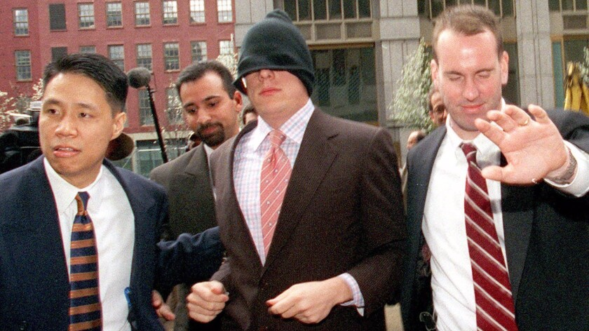Who was that masked man? Dana Giacchetto, center, reports to federal offices in New York to face fraud charges in April 2000.