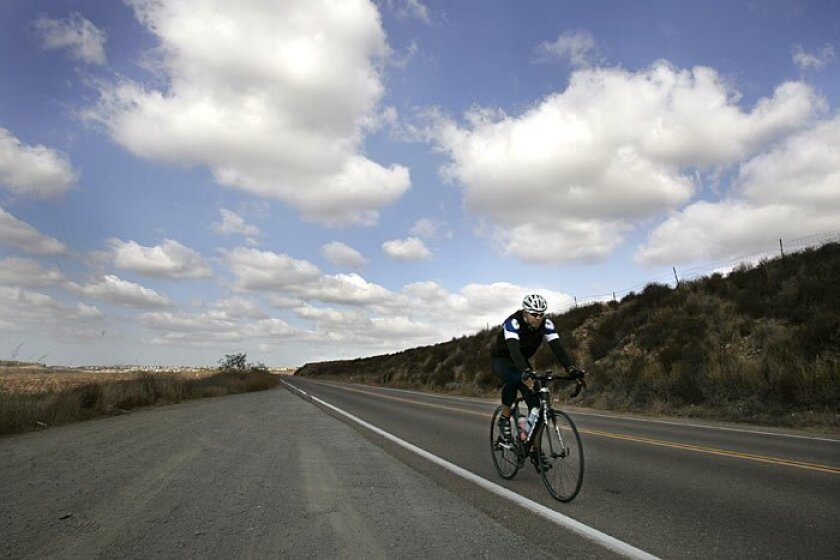 Under a loose canopy of clouds yesterday, a bicyclist pedaled along Otay Lakes Road. A low-pressure system could keep some clouds around and possibly generate sprinkles or light rain tomorrow, the National Weather Service said. Meteorologists are predicting no more than a few hundredths of an inch