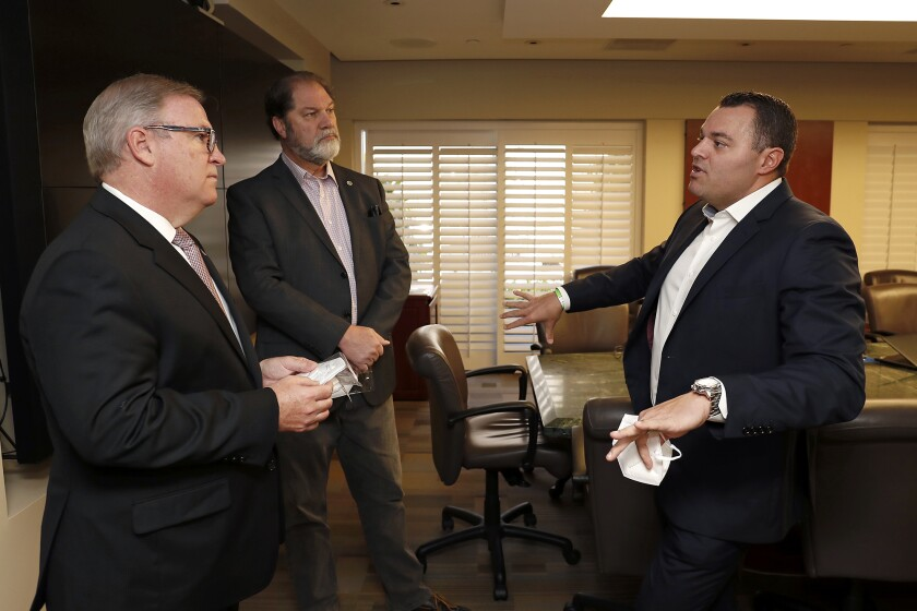 Trevor Theriot, president and chief executive of ManaMed Inc., right, speaks Friday with Robert Braithwaite, president and CEO of Hoag Hospital in Newport Beach, left, and state Sen. John Moorlach (R-Costa Mesa) as Theriot donated 5,000 N95 filtering respirator masks to Hoag.