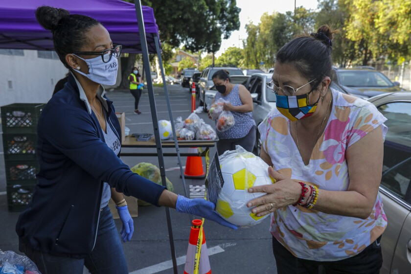 Renata Simril, of LA84 Foundation, distributes sports goods to underserved kids at LAUSD Grab and Go meal center at Thomas Alva Edison School on Wednesday in Los Angeles.