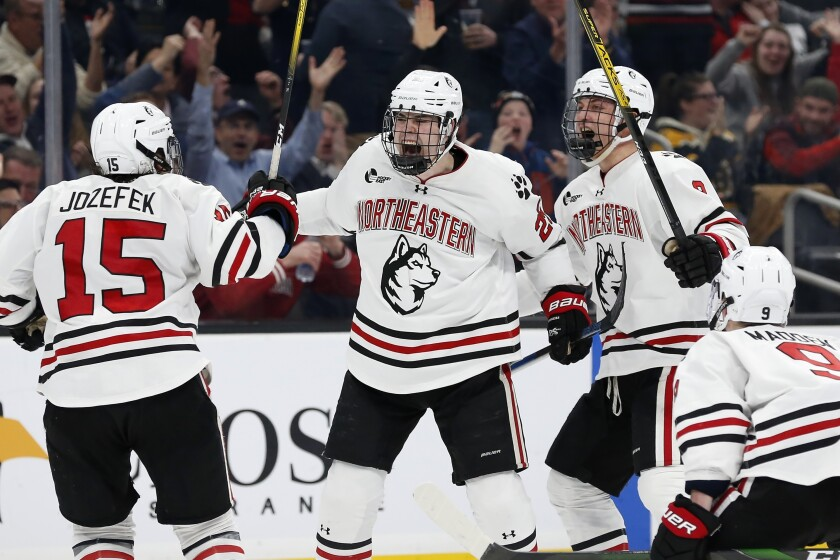 Northeastern's Patrick Schule (25) celebrates his goal with teammates Grant Jozefek (15), Julian Kislin (8) and Tyler Madden (9) during the second period of the Beanpot Tournament championship NCAA college hockey game against Boston University in Boston, Monday, Feb. 10, 2020. (AP Photo/Michael Dwyer)
