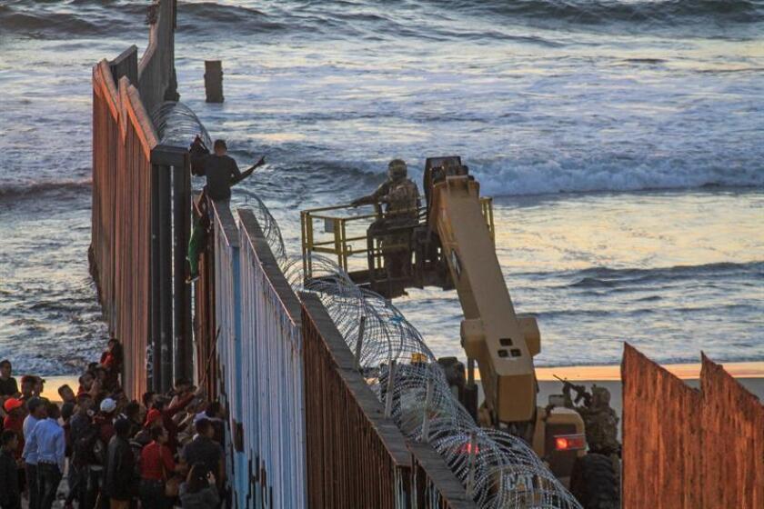 Central American migrants gather at the US-Mexico border fence in Tijuana, Mexico, Nov. 14, 2018. EPA-EFE/Joebeth Terriquez