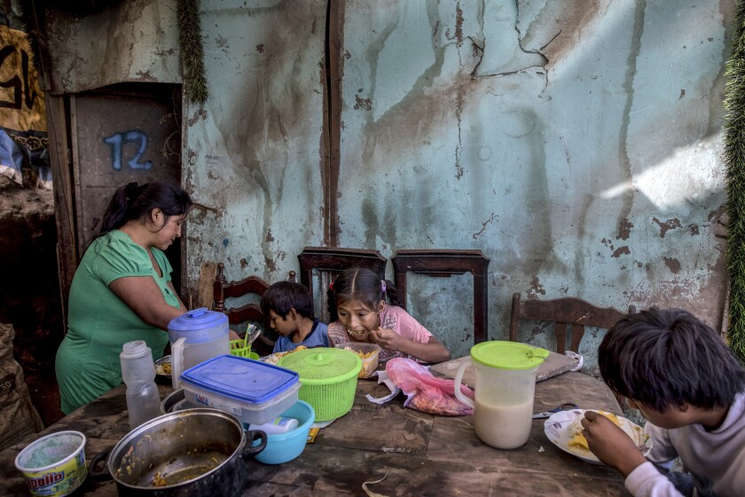 "Consuelo Pascacio's three children dig into a chicken rice stew she picked up at a ""community pot"" in  Lima, Peru."