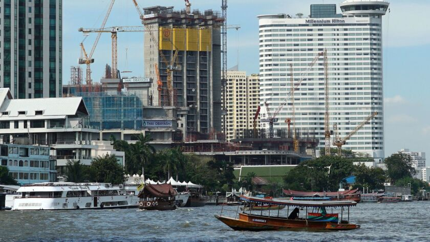 A riverboat taxi crosses the Chao Phraya river in front of massive construction in Bangkok, Thailand.  A United Nations report says Asia's economic outlook for 2017 is strong despite slowing global growth due to sluggish international trade and investment.