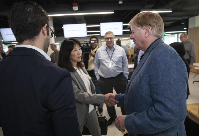 EL SEGUNDO, APRIL 15, 2019: Michele Chan congratulates Los Angeles Times reporters Paul Pringle, ce