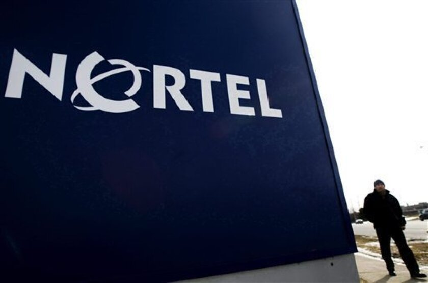 In this Feb. 25, 2009 photo, a man walks past a company sign at a Nortel Networks office tower in Toronto. Bankrupt Canadian telecom group Nortel Networks Corp. on Friday, July 1, 2011, said it is selling all of its remaining patents and patent applications to a consortium including Apple, EMC, Ericsson, Microsoft, Research In Motion and Sony for $4.5 billion in cash. (AP Photo/The Canadian Press, Nathan Denette)