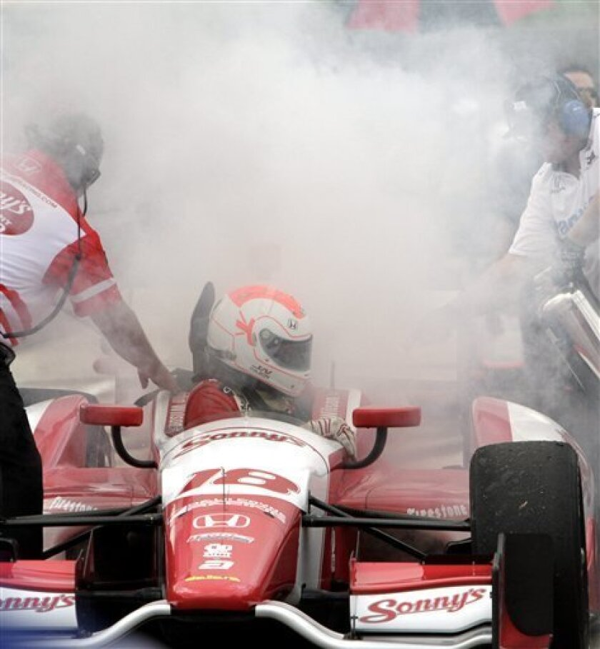 Justin Wilson, of England, climbs out of his car as the pit crew tries to put out a fire in his pit during practice for the IndyCar Grand Prix of Alabama auto race at Barber Motorsports Park on Friday, March 30, 2012, in Birmingham, Ala.  (AP Photo/Butch Dill)